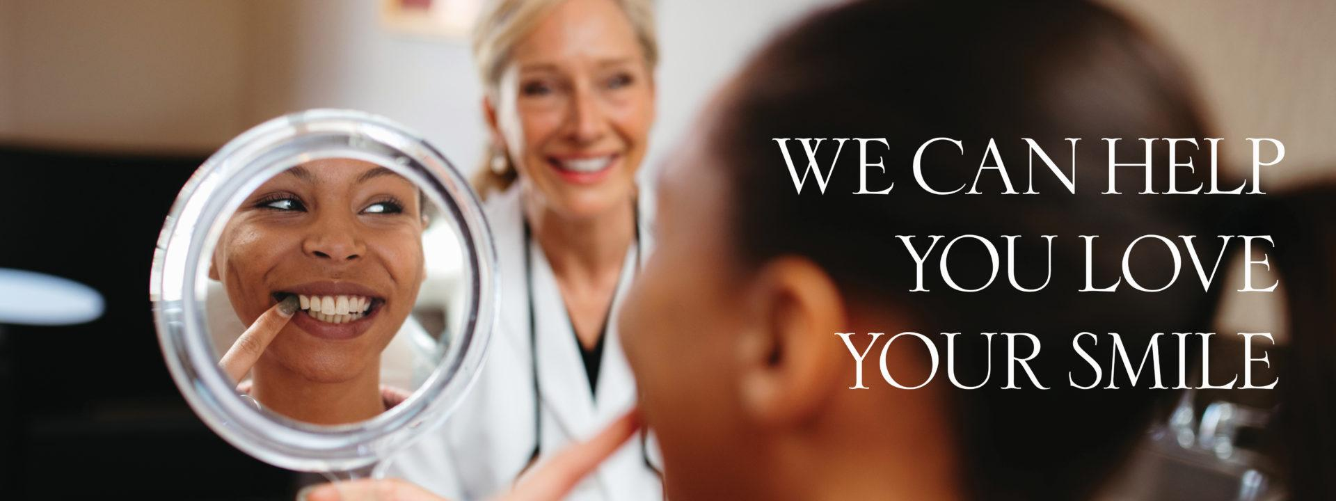 Woman looking into a mirror, pointing at her tooth that she wants to change while the dentist looks on. Text: We can help you love your smile. Angus Dentistry, Midlothian