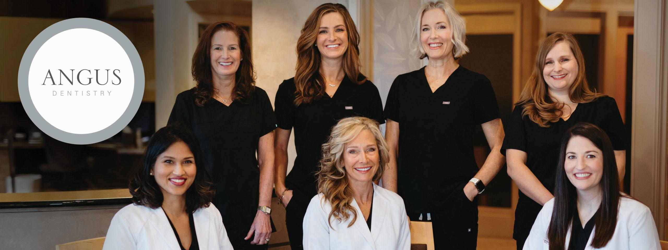 Seven Women Inside Dentist Office. 4 dressed in black scrubs who are standing, and three doctors in lab coats are sitting.